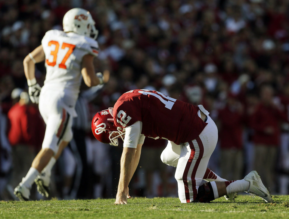 Photo - Oklahoma's Landry Jones (12) gets up slowly after being knocked down by Oklahoma State's Alex Elkins (37) in the second quarter during the Bedlam college football game between the University of Oklahoma Sooners (OU) and the Oklahoma State University Cowboys (OSU) at Gaylord Family-Oklahoma Memorial Stadium in Norman, Okla., Saturday, Nov. 24, 2012. Photo by Nate Billings , The Oklahoman