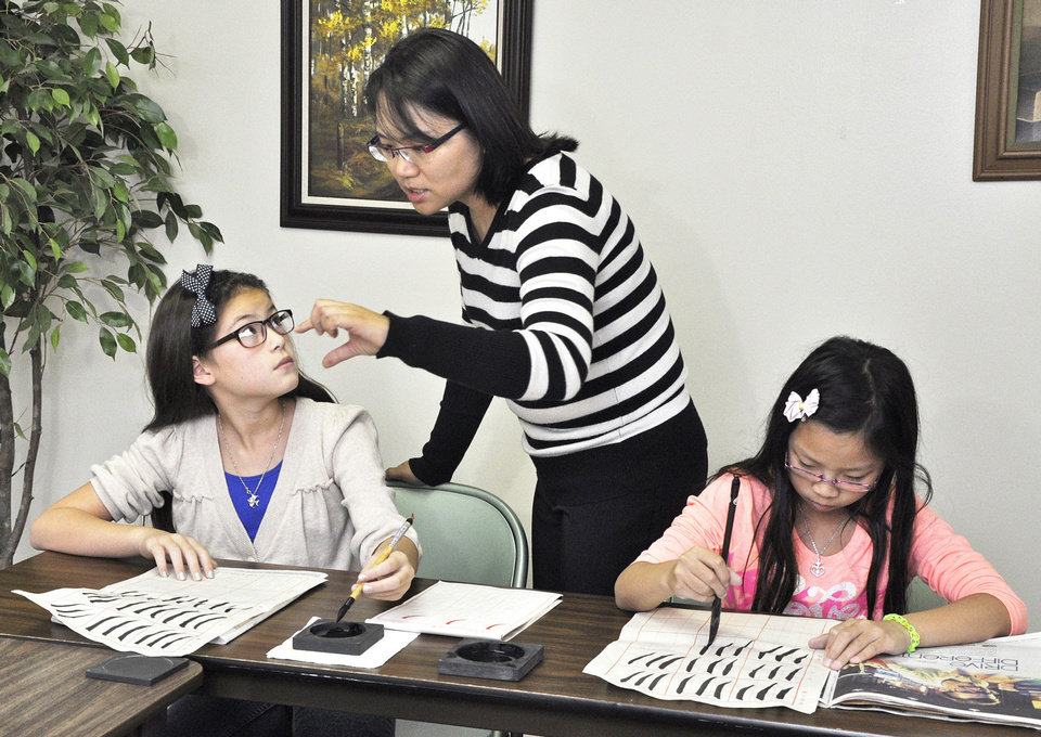 Photo - Calligraphy instructor Peggy Tsai, center, helps Maelin Bowen, left, and Anne Hsieh, right, with their work during Chinese culture classes at Trinity International Baptist Church Sunday, October 6, 2013. Photo by M. Tim Blake, for The Oklahoman