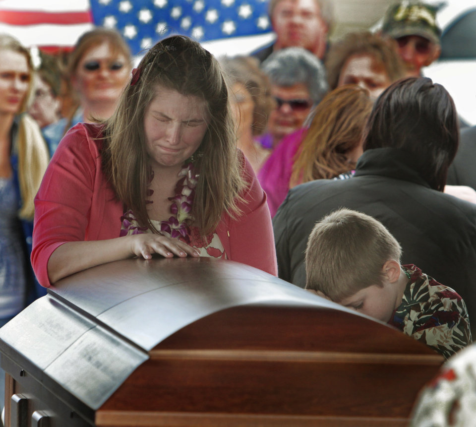 Sgt Lindsey McKenna and middle son Michael, 7, stand at the casket of husband/father Staff Sgt. Allen R. McKenna Jr. at graveside services. on Tuesday, March 6, 2012, in Purcell, Okla.  McKenna was killed in Afghanistan of February, 21.  Photo by Steve Sisney, The Oklahoman