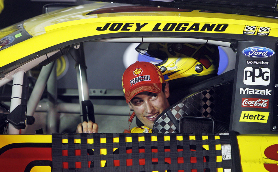 Photo - Driver Joey Logano peeks out his window as he pulls into victory lane after winning a NASCAR Sprint Cup Series auto race at Bristol Motor Speedway on Saturday, Aug. 23, 2014, in Bristol, Tenn. (AP Photo/Wade Payne)