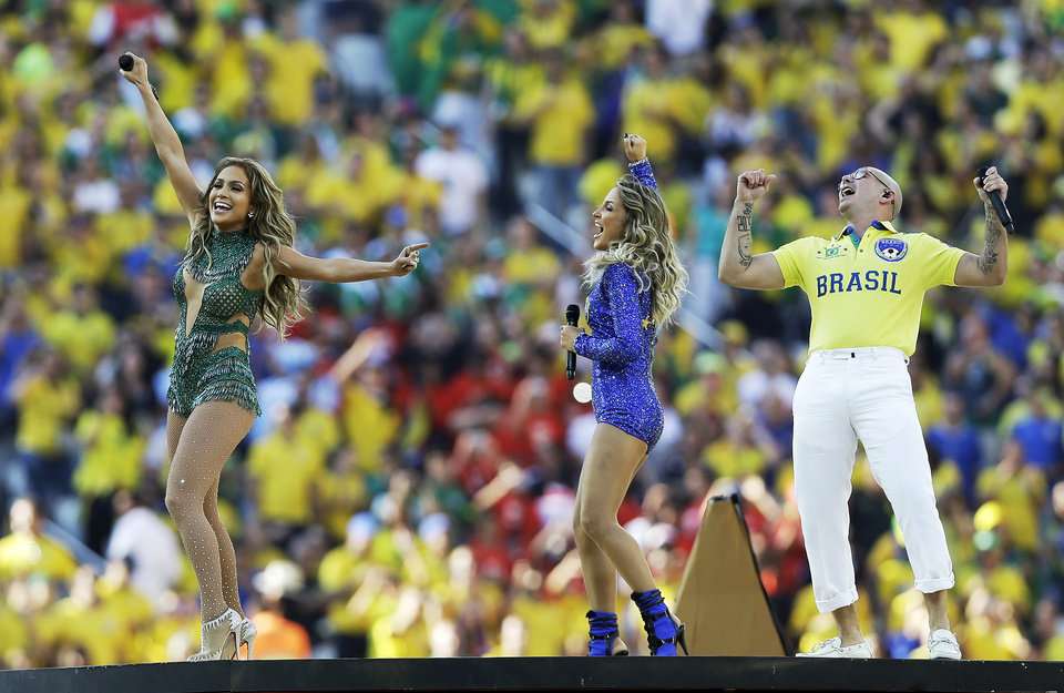 Photo - In this Thursday, June 12, 2014 photo, Jennifer Lopez, left, Brazilian singer Claudia Leitte and rapper Pitbull perform during the opening ceremony ahead of the group A World Cup soccer match between Brazil and Croatia, the opening game of the tournament, in the Itaquerao Stadium in Sao Paulo, Brazil. (AP Photo/Kirsty Wigglesworth)