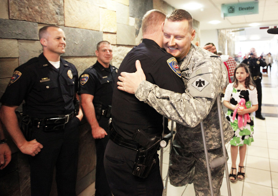 Photo - Edmond police officer Jason Stearns welcomes home fellow officer Kyle Stoy, who was injured in Afghanistan and is a member of the  National Guard. PHOTO BY SARAH PHIPPS, THE OKLAHOMAN