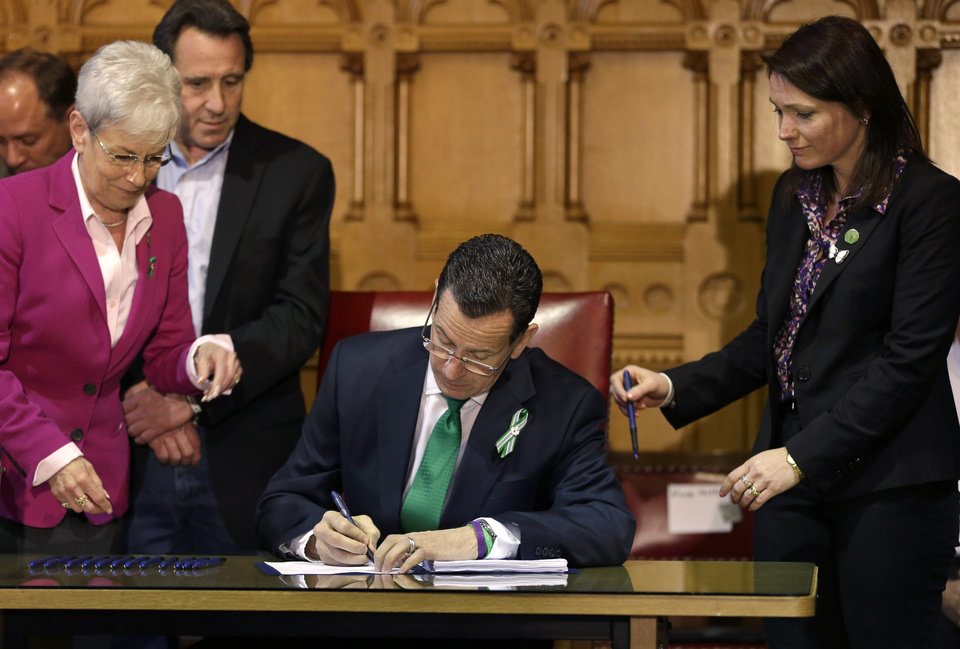 Photo - Connecticut Gov. Dannel P. Malloy, center, signs legislation at the Capitol in Hartford, Conn., Thursday, April 4, 2013, that includes new restrictions on weapons and large capacity ammunition magazines, a response to last year's deadly school shooting in Newtown. Neil Heslin, behind left, father of Sandy Hook shooting victim Jesse Lewis, Nicole Hockley, right, mother of Sandy Hook School shooting victim Dylan, and Conn. Lt. Gov. Nancy Wyman, left, look on. The legislation adds more than 100 firearms to the state's assault weapons ban, sets eligibility rules for buying ammunition, and creates what officials have called the nation's first dangerous weapon offender registry. (AP Photo/Steven Senne)