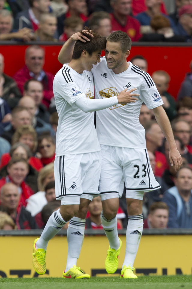 Photo - Swansea City's Ki Sung-Yeung, left, celebrates with teammate Gylvi Sigurdsson after scoring against Manchester United during their English Premier League soccer match at Old Trafford Stadium, Manchester, England, Saturday Aug. 16, 2014. (AP Photo/Jon Super)