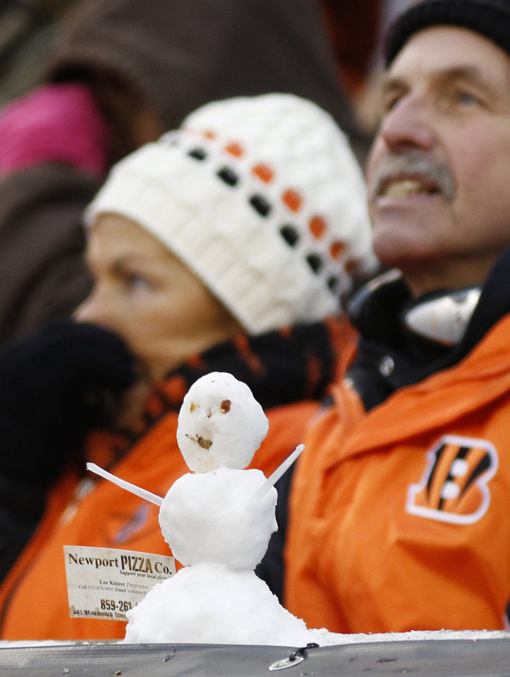 Photo - Cincinnati Bengals fans are bundled up behind a snowman in the second half of an NFL football game against the Indianapolis Colts, Sunday, Dec. 8, 2013, in Cincinnati. Cincinnati won 42-28. (AP Photo/David Kohl)