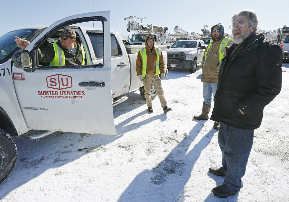 Home owner Bill Stanhope, left, of Pembroke, Mass., asks utility workers from South Carolina when his power might be returned at a staging area at the Hanover Mall in Hanover, Mass., Sunday, Feb. 10, 2013. A howling storm across the Northeast left the New York-to-Boston corridor shrouded in 1 to 3 feet of snow Saturday, stranding motorists on highways overnight and piling up drifts so high that some homeowners couldn't get their doors open. More than 650,000 homes and businesses were left without electricity. (AP Photo/Charles Krupa)