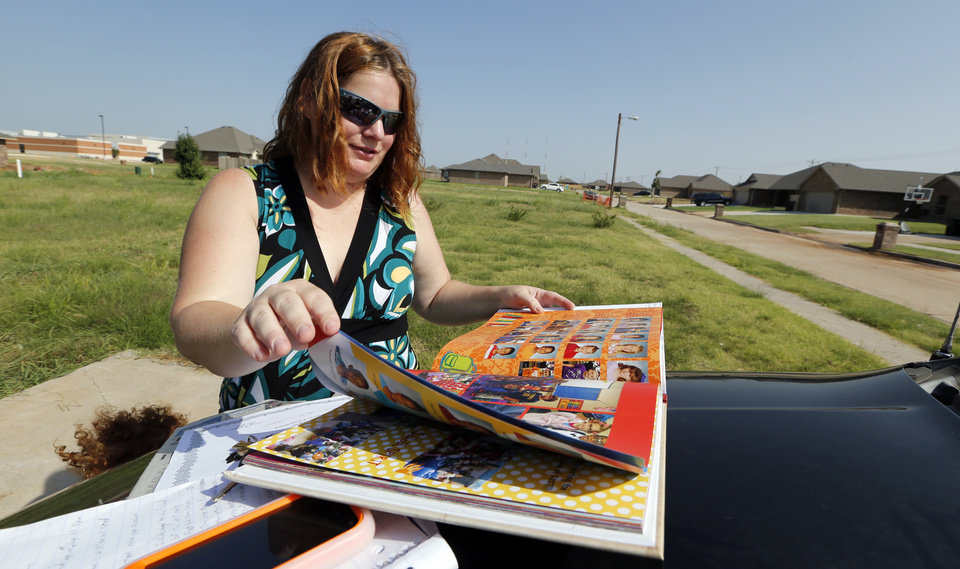 Photo - Lora Trammell shows photos of her son, Porter, in a Plaza Towers Elementary School yearbook. Porter survived the May 20, 2013, tornado at the school, but was not allowed to attend the school this year because their house hasn't been rebuilt. The school is visible in the background.  Photo by Steve Sisney, The Oklahoman  STEVE SISNEY -  THE OKLAHOMAN