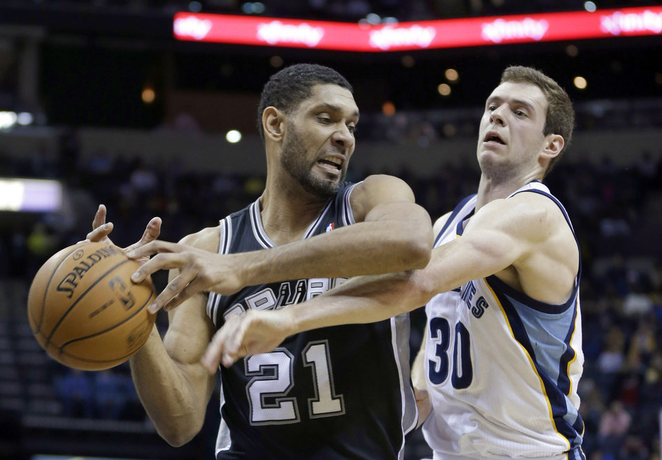 Photo - Memphis Grizzlies' Jon Leuer (30) hits the ball away from San Antonio Spurs' Tim Duncan (21), of U.S. Virgin Islands, in the first half of an NBA basketball game in Memphis, Tenn., Tuesday, Jan. 7, 2014. (AP Photo/Danny Johnston)
