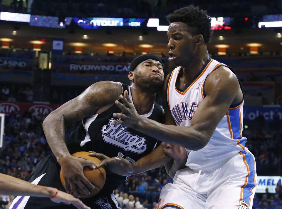 Photo - Sacramento Kings center DeMarcus Cousins (15) drives into Oklahoma City Thunder center Hasheem Thabeet during the first quarter of an NBA basketball game in Oklahoma City, Friday, March 28, 2014. (AP Photo/Sue Ogrocki)