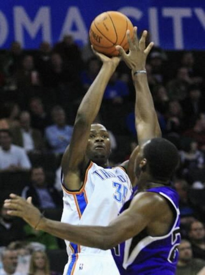 Oklahoma City Thunder forward  Kevin  Durant, left, shoots as Sacramento Kings guard Desmond Mason, right, defends, in the third quarter of an NBA preseason basketball game in Oklahoma City, Thursday, Oct. 22, 2009.  Durant had 15 points for the Thunder but Sacramento won the game 104-89. (AP Photo)