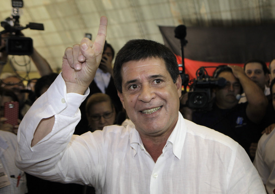 Photo - Paraguay's Colorado Party's Presidential candidate Horacio Cartes gestures before casts his vote during general elections in Asuncion, Paraguay, Sunday, April 21, 2013. The elections are an important milestone in Paraguay's attempt to regain the international acceptance it lost when neighboring nations objected to the fast-track removal of President Fernando Lugo. (AP Photo/Jorge Saenz)