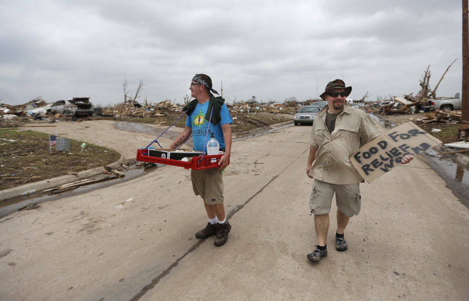 Jeff Leach, left, and Andrew Wagner pass out food to workers in the Plaza Towers neighborhood in Moore, Okla., Friday, May, 24, 2013. The pair was from Adventure Christian Community in Davenport, Iowa. Photo by Sarah Phipps, The Oklahoman