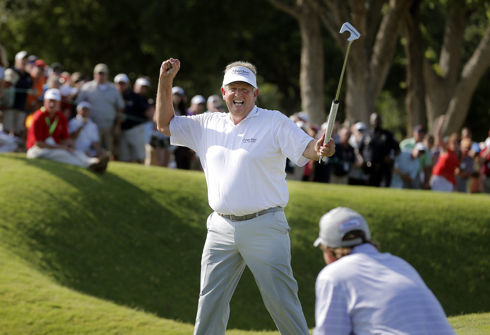 Photo - Colin Montgomerie celebrates his putt on the 18th hole during a 3-hole playoff as Gene Sauers looks on in the final round of the U.S. Senior Open golf tournament at Oak Tree National in Edmond, Okla., Sunday, July 13, 2014. Photo by Sarah Phipps, The Oklahoman