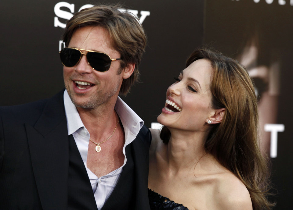 Photo - FILE - In this Monday, July 19, 2010, file photo, cast member Angelina Jolie, right and Brad Pitt arrive at the premiere of