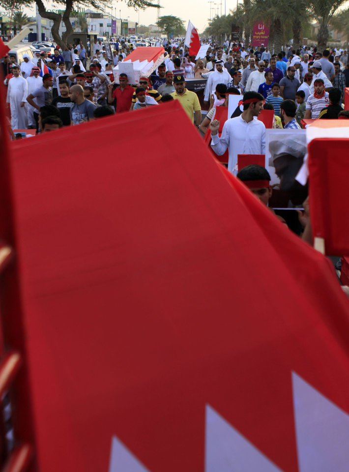 Photo -   Anti-government protesters carry symbolic coffins draped in Bahraini flags Friday, May 4, 2012, during a mass march in Barbar, Bahrain, west of the capital of Manama, in memory of those who have died in the past year's pro-democracy uprising. Protesters called for political prisoners to be freed and the opposition parties that organized the march said in a statement that newly approved changes to the nation's constitution are merely cosmetic and