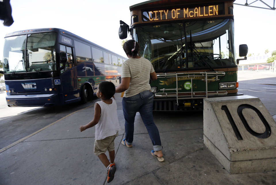 Photo - In this June 20, 2014 photo, Cindy Jimenez, 26, from Olancho, Honduras, and her son depart the bus station in McAllen, Texas. Jimenez crossed illegally into the U.S. (AP Photo/Eric Gay)