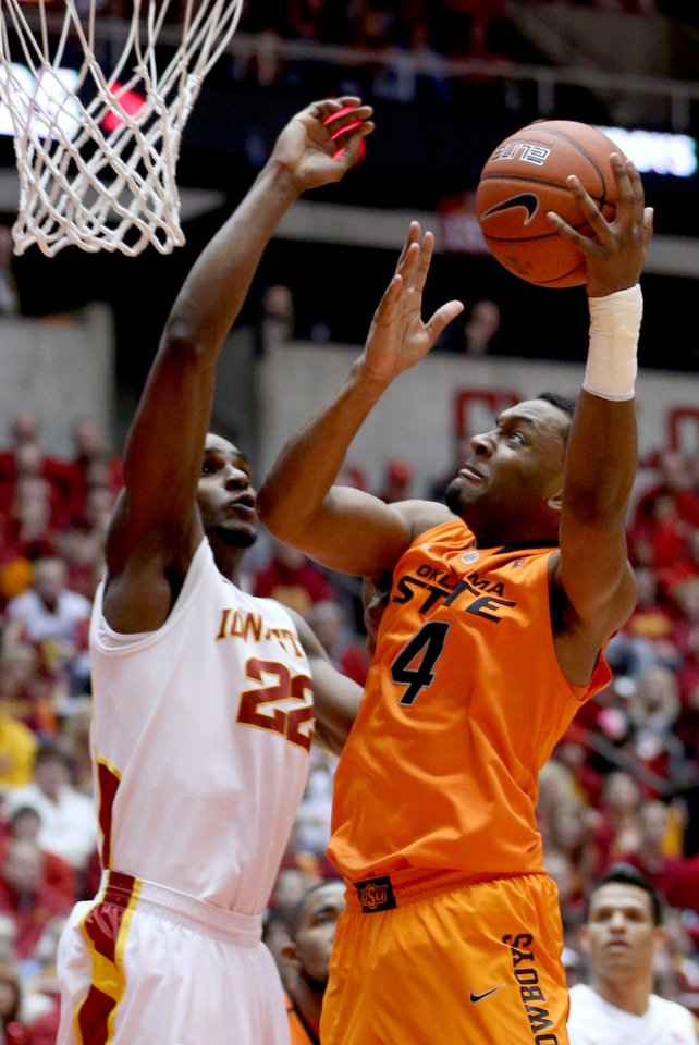 Oklahoma State's Brian Williams (4) shoots over Iowa State forward Anthony Booker during the first half of an NCAA college basketball game, Wednesday, March 6, 2013, in Ames, Iowa. (AP Photo/Justin Hayworth)