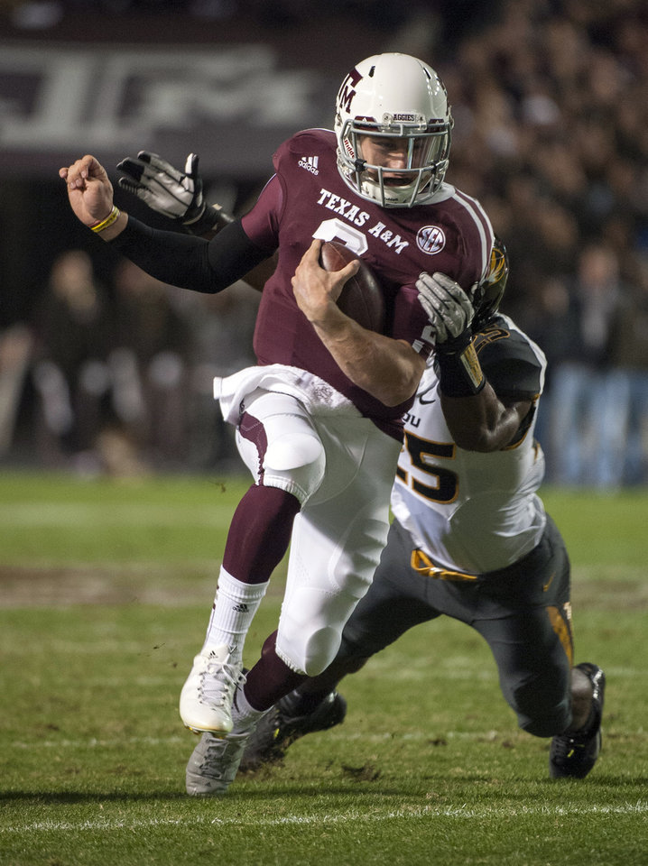 Photo -   Texas A&M's Johnny Manziel, front, runs through Missouri's Zaviar Gooden (25) during the first quarter of an NCAA college football game on Saturday, Nov. 24, 2012, in College Station, Texas. (AP Photo/Dave Einsel)