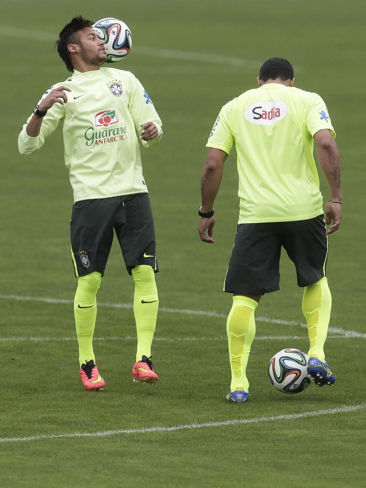 Photo - Brazil's Neymar, left, controls the ball during a practice session at the Granja Comary training center in Teresopolis, Brazil, Wednesday, May 28, 2014. Brazil will host the World Cup soccer tournament that starts in June. (AP Photo/Hassan Ammar)