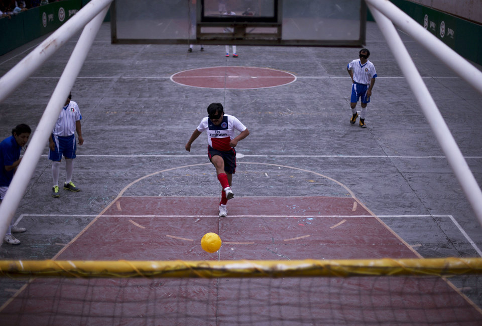 Photo - In this Sunday, June 8, 2014 photo, a player scores off a penalty, in a mixed-team match following the league final, in Mexico City. Since players follow the movement of the ball by its sound, airborne shots are particularly hard for goalkeepers to anticipate. (AP Photo/Rebecca Blackwell)