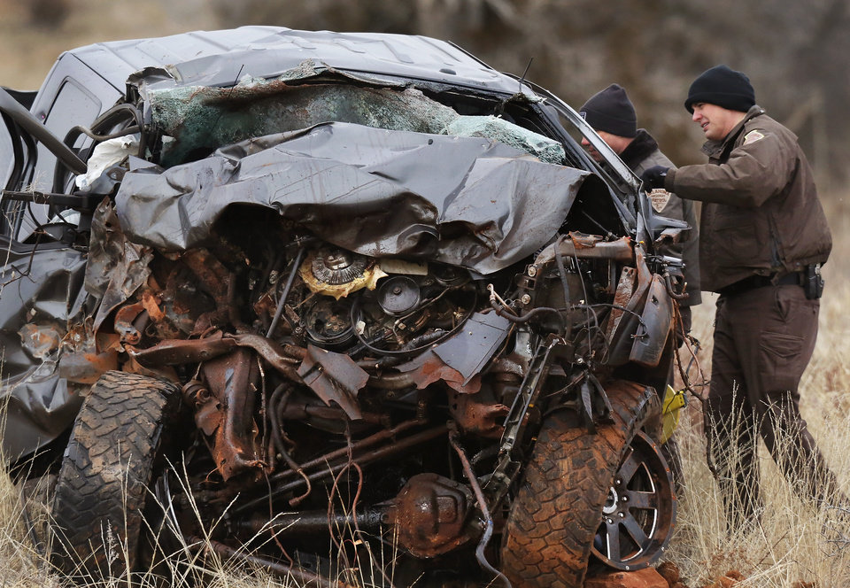 Photo - OHP investigators look at the wreckage of a 2011 Ford pickup truck after it was pulled from a ravine where it landed after the driver ran off a two lane blacktop road east of Dill City.  This truck was driven by suspect Quentin Lee Johnson, 27 of Sentinel. Two officers died in a separate crash as they pursued this vehicle near Dill City. A Burns Flat police officer and an undersheriff for the Washita County Sheriff's Department died in a car crash on Thursday, Jan. 23, 2014, at a rural intersection about one mile south of Dill City.  According to OHP spokesman, the lawmen became involved in a high-speed pursuit  when a Washita County man fled as the undersheriff approached him to serve a felony warrant Thursday morning.  That same suspect died about the same time in another crash about three miles east of the location where the law officers collided. Dill City is located 75 miles west of Oklahoma City. Photo by Jim Beckel, The Oklahoman