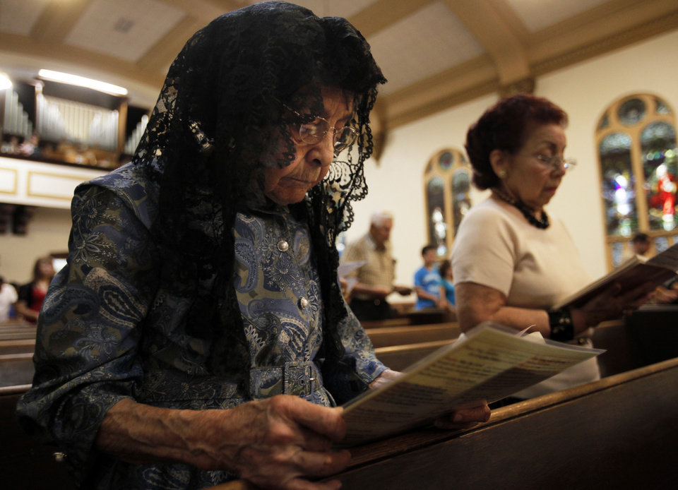 Photo - Margarita Martinez, 94, of Oklahoma City, reads the church program at Little Flower Church before service. Martinez has been a member of the church since 1926. Photo by K.T. KING, The Oklahoman  KT King - KT KING