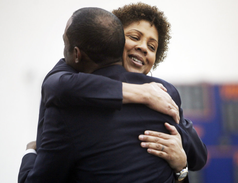 Photo - Women's basketball great Cheryl Miller hugs Langston athletic director Mike Garrett at a press conference where she was introduced as the head coach of Langston's women's basketball program on Tuesday, April 29, 2014 Photo by KT King, The Oklahoman
