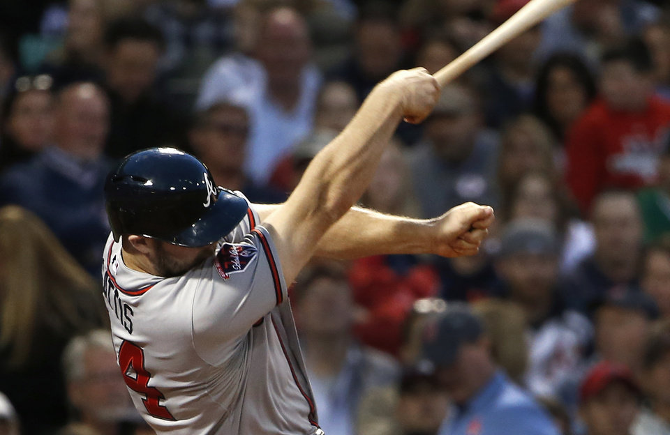 Photo - Atlanta Braves' Evan Gattis swings and misses a pitch with one hand on the bat during the fourth inning of a baseball game against the Boston Red Sox at Fenway Park in Boston, Thursday, May 29, 2014. (AP Photo/Winslow Townson)