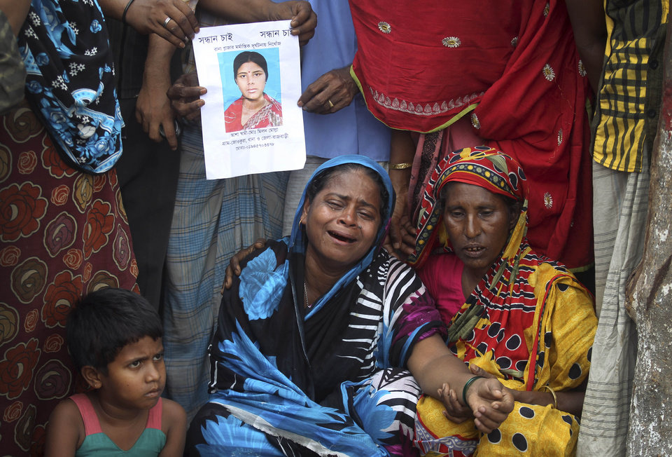 Photo - Women cry as others hold a portrait of her missing relative at the site of the collapsed garment factory building on Tuesday, April 30, 2013 in Savar, near Dhaka, Bangladesh.   A top Bangladesh court on Tuesday ordered the government to