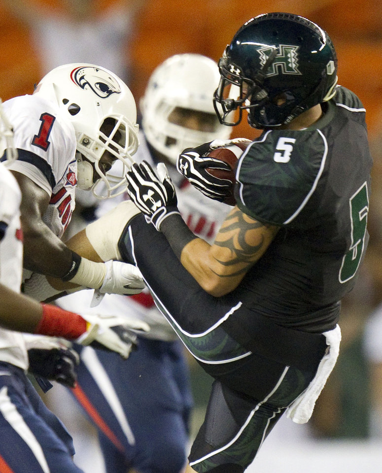 Photo - Southern Alabama safety B.J. Scott (1) manages to get a hold of and tackles Hawaii wide receiver Billy Ray Stutzmann (5) in the first quarter of an NCAA college football game Saturday, Dec. 1, 2012, in Honolulu. (AP Photo/Eugene Tanner)