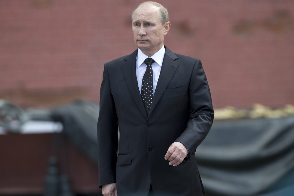 Photo - In this photo taken on Sunday, June  22, 2014, Russian Vladimir Putin takes part in a wreath laying ceremony at the Tomb of the Unknown Soldier outside Moscow's Kremlin Wall, in Moscow, Russia, to mark the 73rd anniversary of the Nazi invasion of the Soviet Union. Russian news agencies say President Vladimir Putin has asked parliament to cancel a resolution that sanctions the use of military force in Ukraine. Putin wrote to the head of parliament's upper house asking that a March 1 request authorizing the use of force in neighboring Ukraine be withdrawn. (AP Photo/Alexander Zemlianichenko)