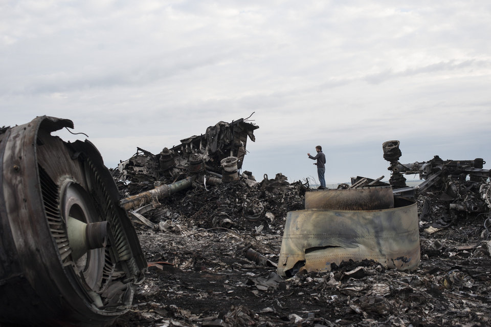 Photo - A journalist, background, takes a photo at the crash site of a Malaysia Airlines jet near the village of Hrabove, eastern Ukraine, Saturday, July 19, 2014. World leaders demanded Friday that pro-Russia rebels who control the eastern Ukraine crash site of Malaysia Airlines Flight 17 give immediate, unfettered access to independent investigators to determine who shot down the plane. (AP Photo/Evgeniy Maloletka)