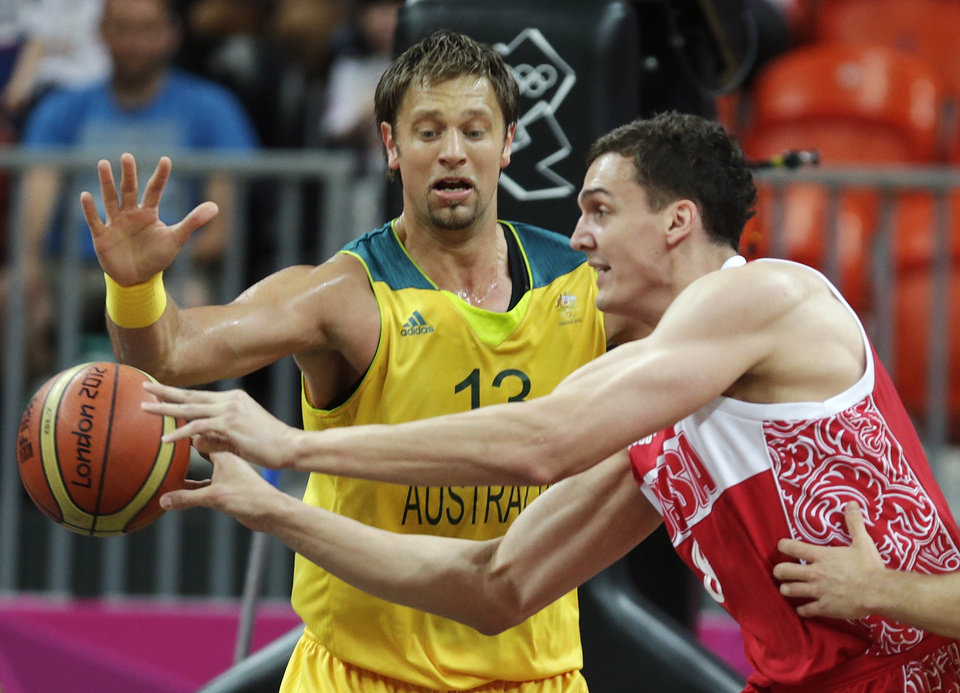 Photo -   Russia's Sasha Kaun, right, passes as he is pressured by Australia's David Andersen during a men's basketball game at the 2012 Summer Olympics, Monday, Aug. 6, 2012, in London. (AP Photo/Charles Krupa)