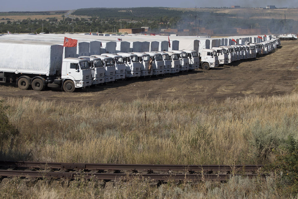 Photo - An aid convoy is parked in Voronezh, about 28 kilometers (17 miles) from Ukrainian border, Rostov-on-Don region, Russia, Friday, Aug. 15, 2014. The Ukrainian government threatened to use all means available to block the convoy if the Red Cross was not allowed to inspect the cargo. Such an inspection would ease concerns that Russia could use the aid shipment as cover for a military incursion in support of the separatists, who have come under growing pressure from government troops. (AP Photo/Pavel Golovkin)