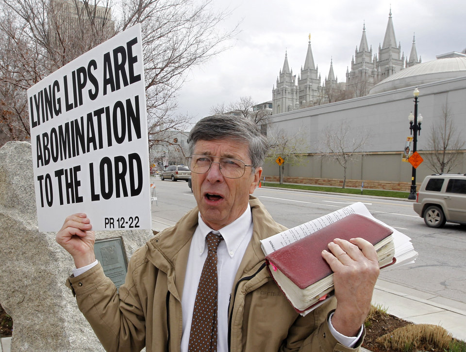 Photo - A unidentified man who called himself Brother Carl carries a sign outside the Conference Center during the 183rd Annual General Conference of The Church of Jesus Christ of Latter-day Saints Saturday, April 6, 2013, in Salt Lake City.  More than 100,000 members of the church have gathered in Salt Lake City to hear words of inspiration and guidance for daily living from the faith's senior leaders.  (AP Photo/Rick Bowmer)