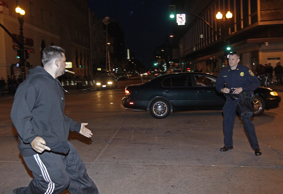 A protestor, left, runs as he attempts to evade police before being arrested during a May Day protest on Tuesday, May 1, 2012 in Oakland, Calif. Hundreds of activists across the U.S. joined the worldwide May Day protests on Tuesday, with Occupy Wall Street members in several cities leading demonstrations and in some cases clashing with police. (AP Photo/Ben Margot)