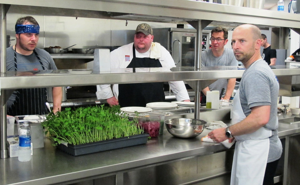 Photo - Chefs David Henry, Tabb Singleton, Alain Buthion and Marc Dunham listen for instructions on the line at the OK Chefs Relief Pop-Up restaurant on Sunday.  DAVE CATHEY - THE OKLAHOMAN