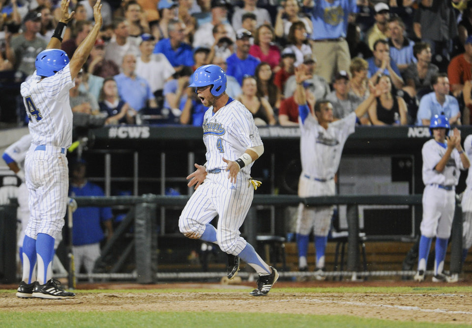 Photo - UCLA's Eric Filia (4) celebrates after he scored against North Carolina on a two-RBI double by Pat Valaika in the seventh inning of an NCAA College World Series baseball game in Omaha, Neb., Friday, June 21, 2013. UCLA's Brian Carroll, left, also scored on the play. (AP Photo/Francis Gardler)