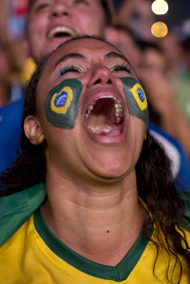 Photo - Brazil soccer fan Talina Simoes celebrates a goal as she watches a live telecast of the World Cup quarterfinal between Brazil and Colombia inside the FIFA Fan Fest area in Taquatinga, Brazil, Friday, July 4, 2014. (AP Photo/Rodrigo Abd)