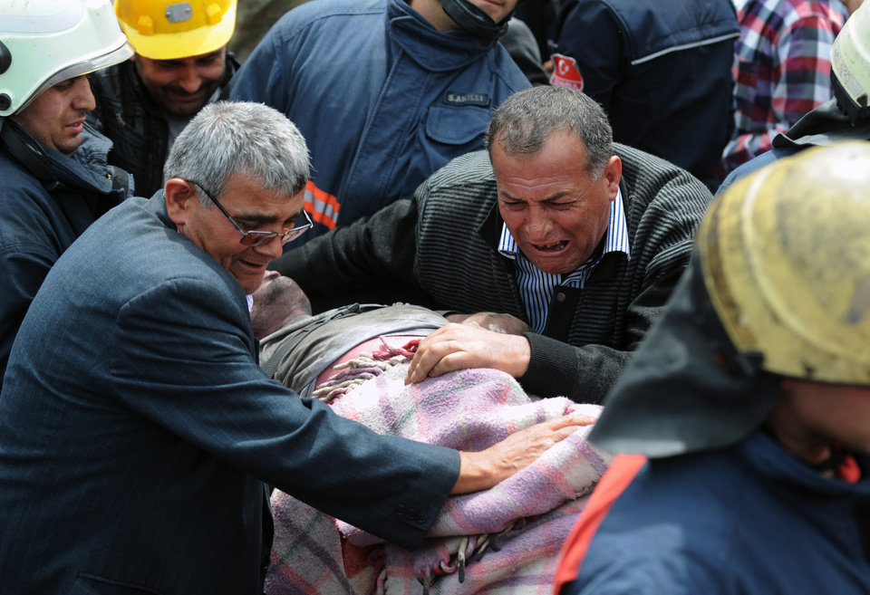 Photo - AP10ThingsToSee - A man cries over the body of a miner being carried outside the coal mine in Soma, Turkey, Wednesday, May 14, 2014. Rescuers desperately raced against time to reach more than 200 miners still trapped underground Wednesday after an explosion and fire at the coal mine on Tuesday killed at least 238 workers. (AP Photo/Depo Photos)