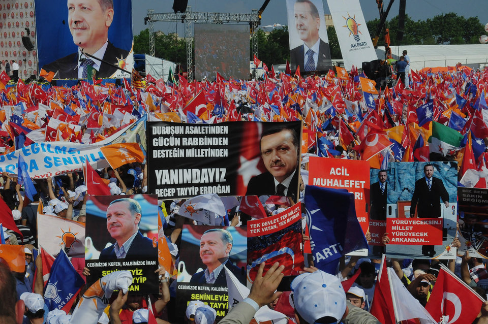 Photo - Supporters of Turkish Prime Minister Recep Tayyip Erdogan wave his posters before he arrives to address a party rally in Istanbul, Turkey, Sunday, June 16, 2013.The banner at the center reads: 'We are with you.' (AP Photo/Burhan Ozbilici)