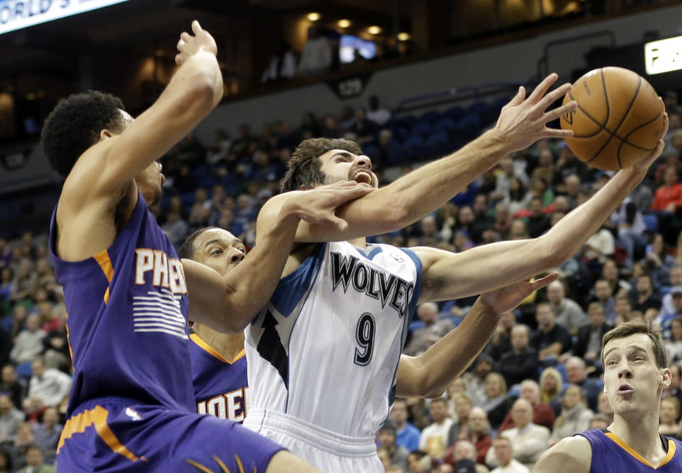 Photo - Minnesota Timberwolves' Ricky Rubio (9), of Spain, attempts a layup as Phoenix Suns' Gerald Green grabs his arm in the first quarter of an NBA basketball game on Wednesday, Jan. 8, 2014, in Minneapolis. (AP Photo/Jim Mone)