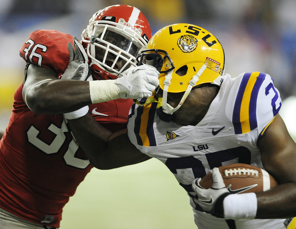 Georgia safety Shawn Williams (36) grabs LSU running back Kenny Hilliard (27) face mask as Hilliard scores a touchdown during the second half of the Southeastern Conference championship NCAA college football game, Saturday, Dec. 3, 2011, in Atlanta. (AP Photo/Stephen Morton) ORG XMIT: GAMS130