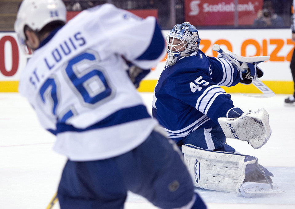 Photo - Toronto Maple Leafs goaltender Jonathan Bernier, right, makes a save on Tampa Bay Lightning right winger Martin St. Louis during the third period of an NHL hockey game in Toronto, Tuesday, Jan. 28, 2014. (AP Photo/The Canadian Press, Frank Gunn)
