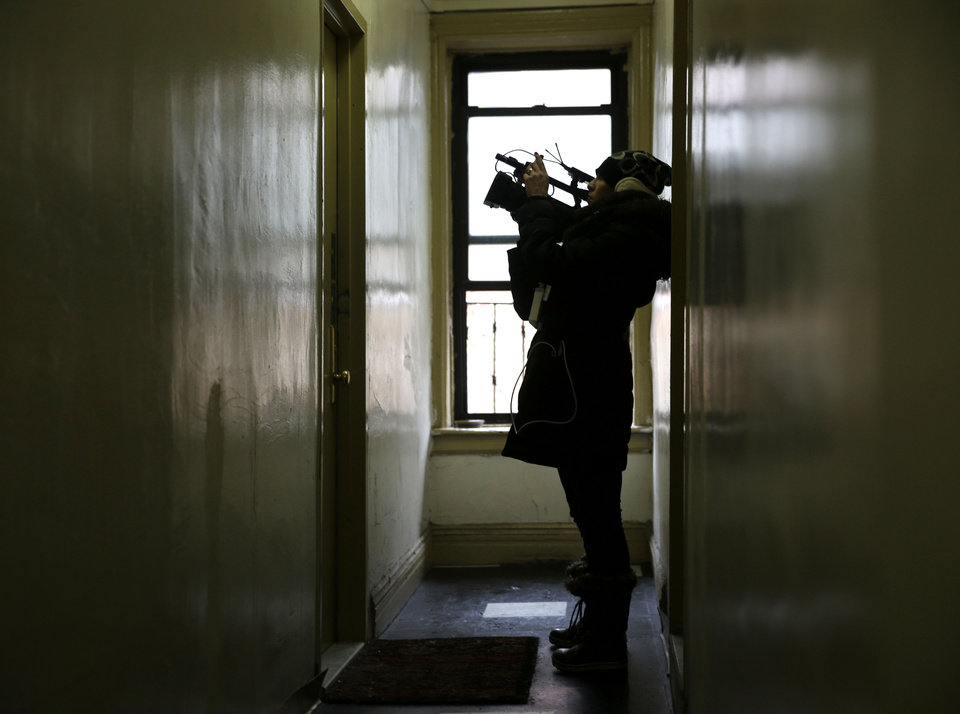 Photo - A reporter films the door of an apartment that was searched by police at 320 Mott St. in New York, Wednesday, Feb. 5, 2014. Four people are in custody on drug charges after police executed search warrants at three apartments in the building. (AP Photo/Seth Wenig)