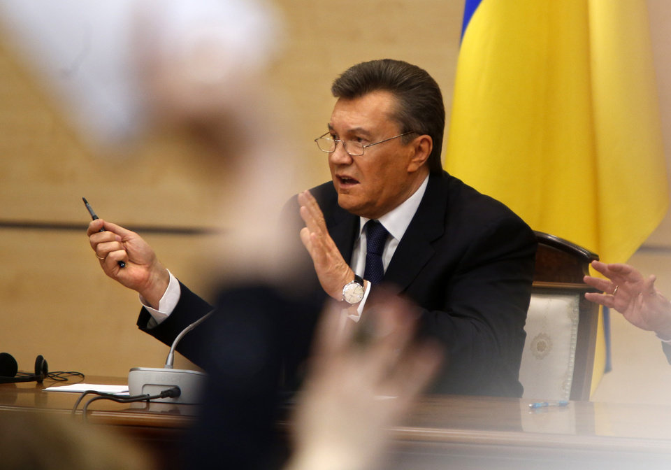 Photo - Ukraine's fugitive President Viktor Yanukovych speaks at a news conference as journalists raise arms to ask questions in Rostov-on-Don, a city in southern Russia about 1,000 kilometers (600 miles) from Moscow, Friday, Feb. 28, 2014. Yanukovych has pledged to fight on for the country's future. (AP Photo/Pavel Golovkin)