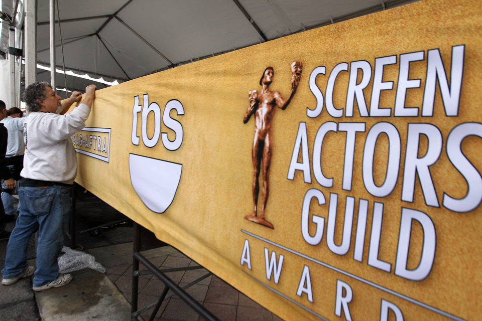 Photo - Workers set up signage on the red carpet before the 19th annual SAG Awards on Saturday, Jan 26, 2013 in Los Angeles. The SAG Awards will be held Jan. 27, 2013. (Photo by Matt Sayles/Invision/AP)