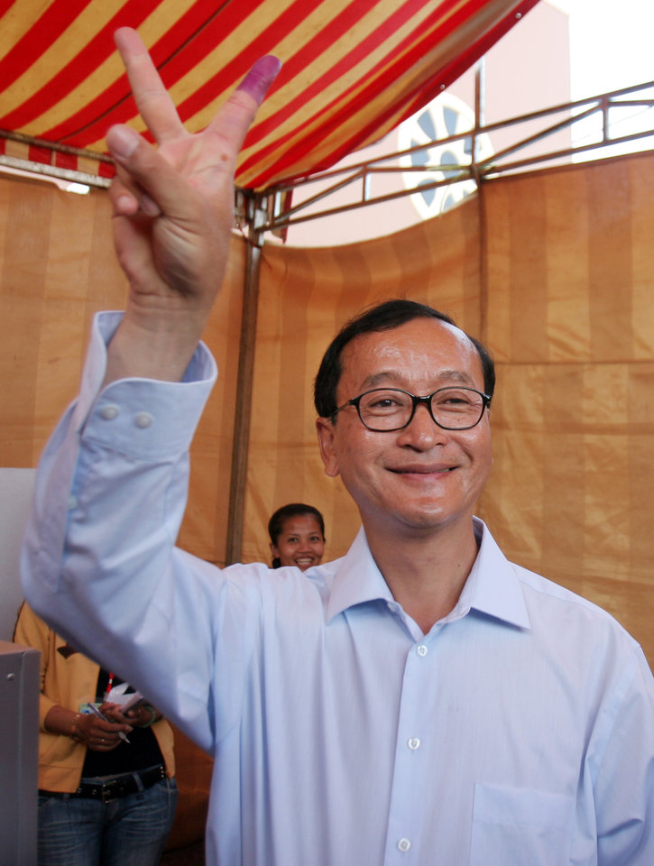 Photo - FILE - IN this April 1, 2007 file photo, Sam Rainsy, the leader of Cambodia's opposition Sam Rainsy Party, shows off a V-sign after casting his ballot at a polling station in Phnom Penh, Cambodia. Thousands of cheering supporters greeted Cambodian opposition leader Sam Rainsy as he returned from self-imposed exile Friday, July 19, 2013 to spearhead his party's election campaign against well-entrenched Prime Minister Hun Sen. (AP Photo/Heng Sinith, File)