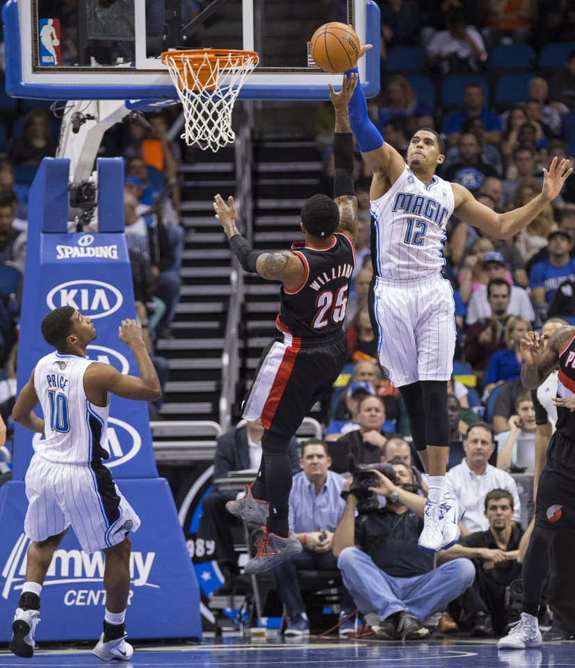 Photo - Orlando Magic's Tobias Harris (12) attempts to block Portland Trail Blazers Mio Williams shot while Ronnie Price (10) watches during the first half of an NBA basketball game in Orlando, Fla., Tuesday, March 25, 2014. (AP Photo/Willie J. Allen Jr.)