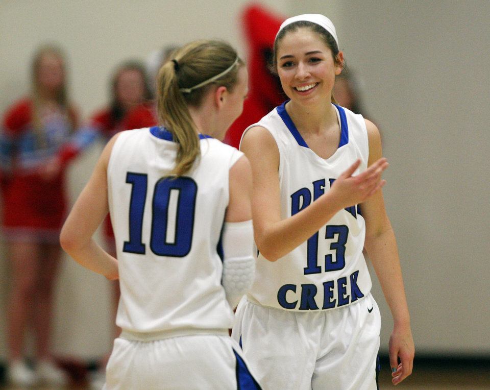 Photo - Edmond Deer Creek's Whitney Jones (13) and Alexa Adair (10) smile at one another following a run during the first quarter of their first round 5A girls playoff game against Collinsville, in Catoosa, on Thursday, March 7, 2013. CORY YOUNG/Tulsa World